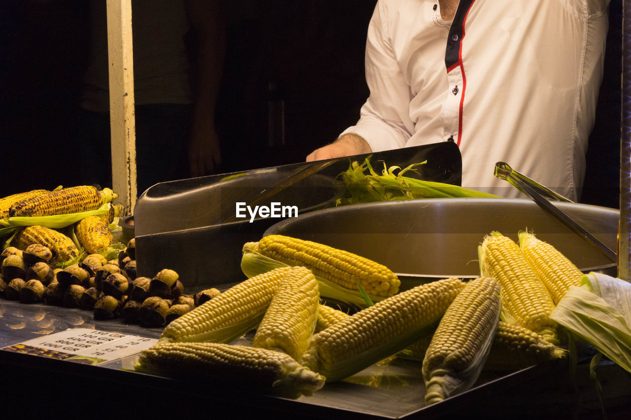 Midsection Of Vendor With Corns At Market