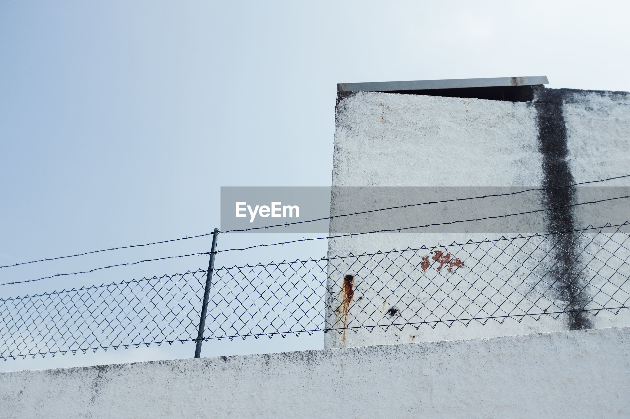 Low angle view of fence by wall against clear sky