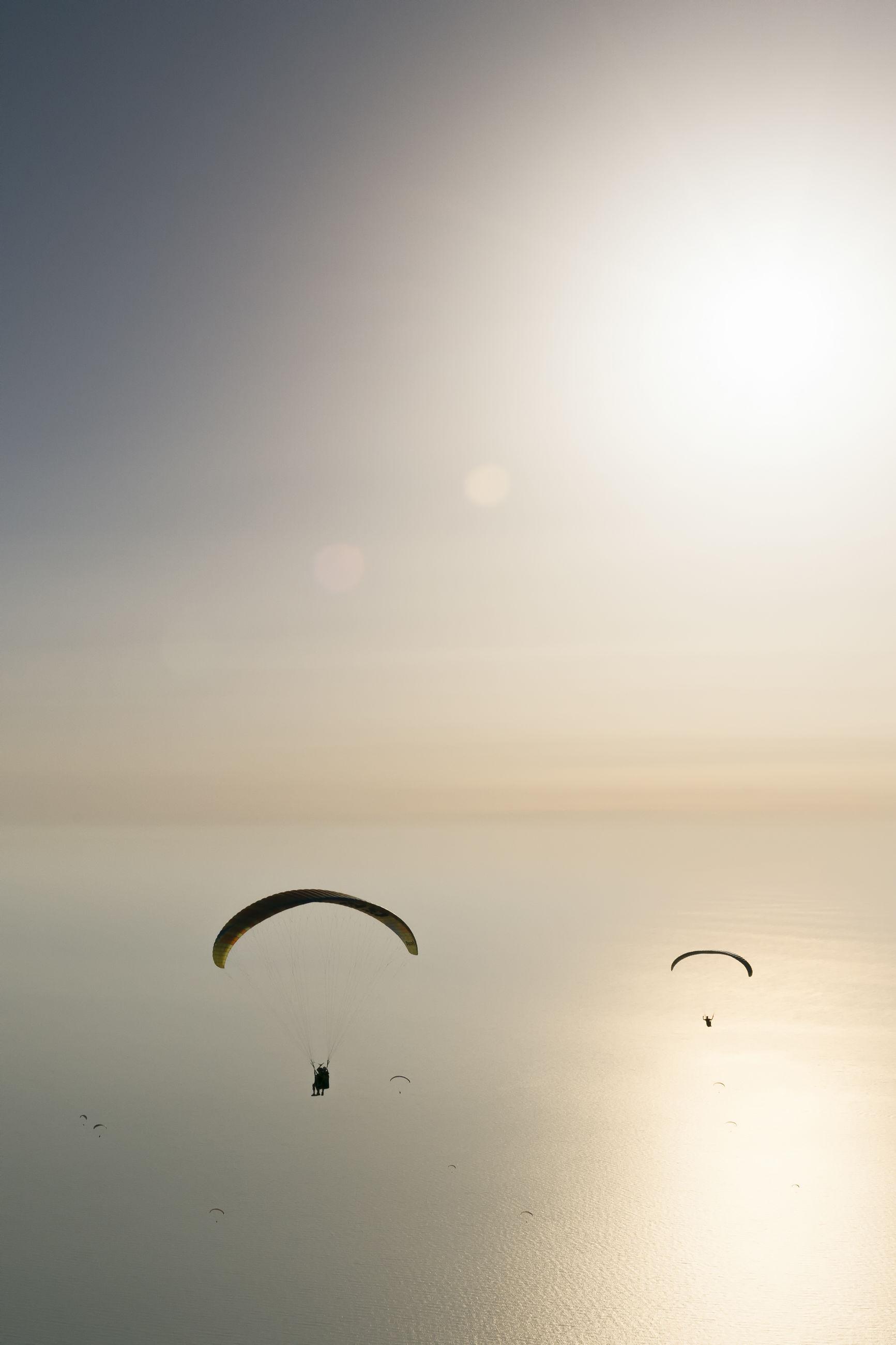 SILHOUETTE OF KITE FLYING OVER SEA AGAINST SKY
