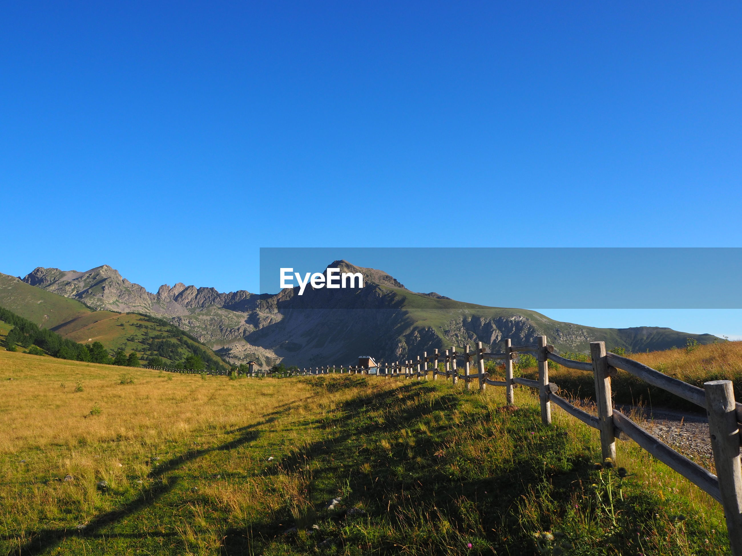 SCENIC VIEW OF FIELD AND MOUNTAINS AGAINST CLEAR BLUE SKY