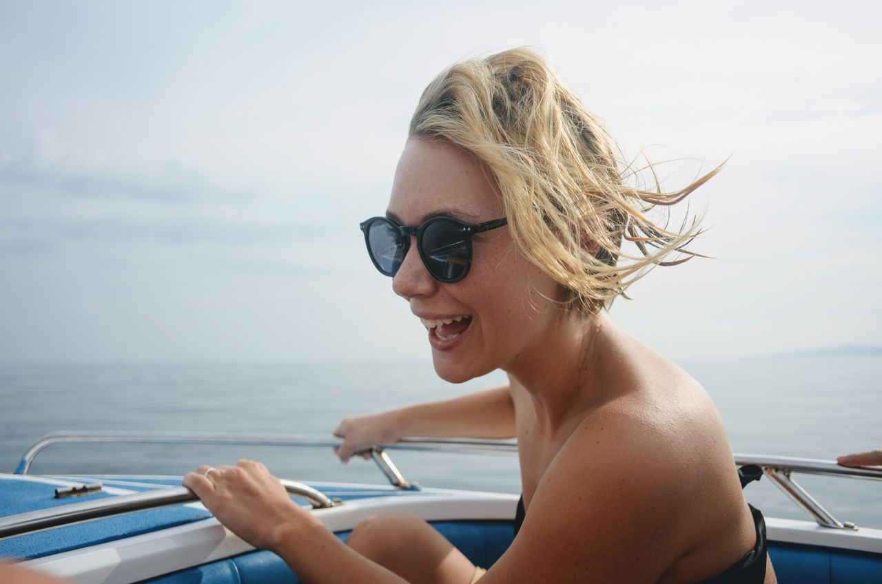 Close-Up Of Cheerful Young Woman Traveling On Boat In Sea