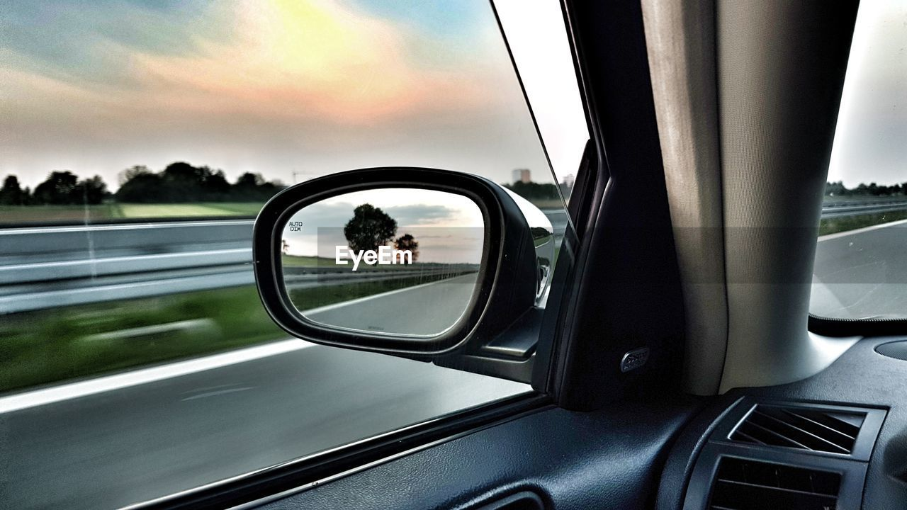 transportation, mode of transportation, land vehicle, sky, glass - material, window, vehicle interior, reflection, car, transparent, motor vehicle, cloud - sky, side-view mirror, car interior, nature, travel, sunset, day, road, close-up, outdoors, road trip