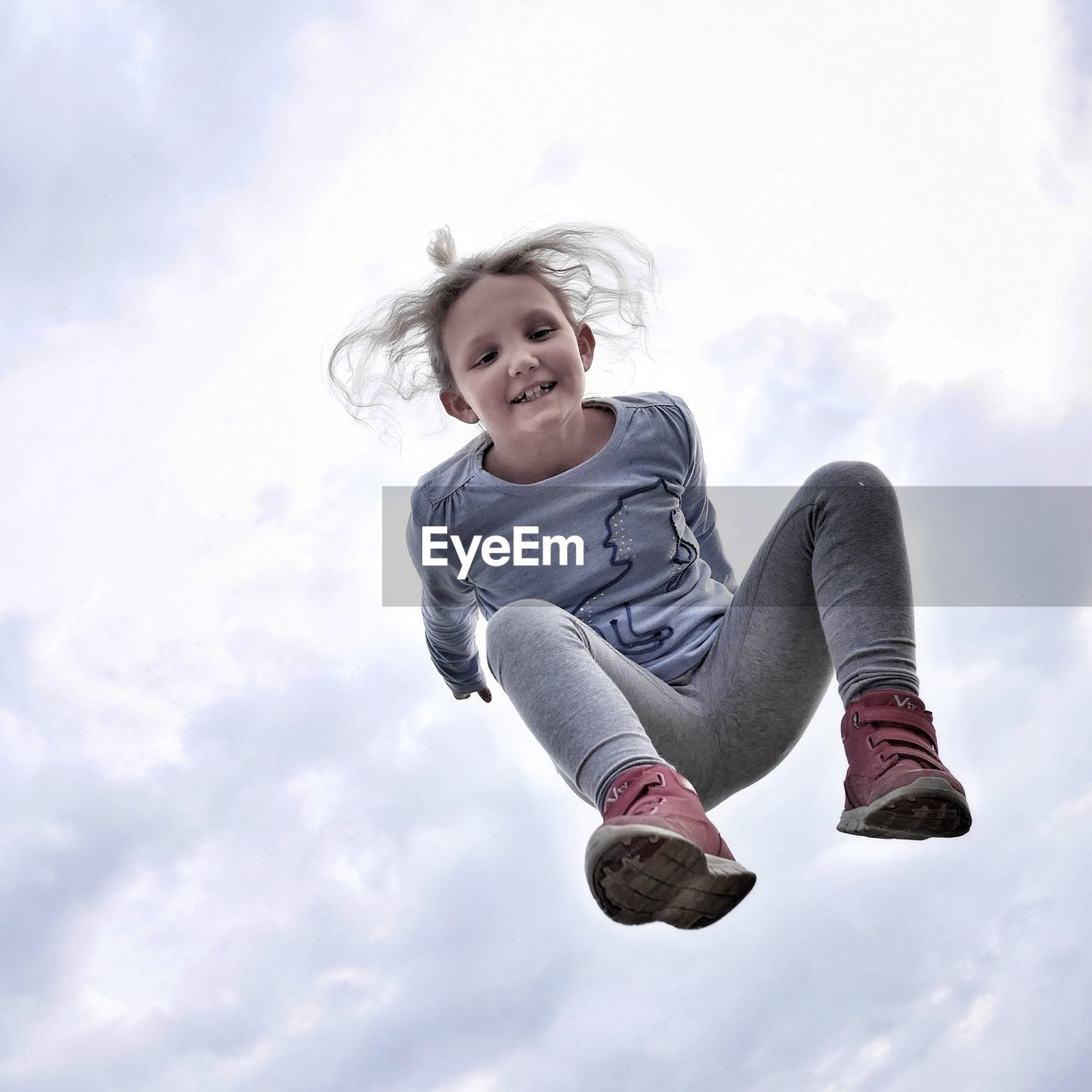 Smiling Girl Jumping Against Cloudy Sky