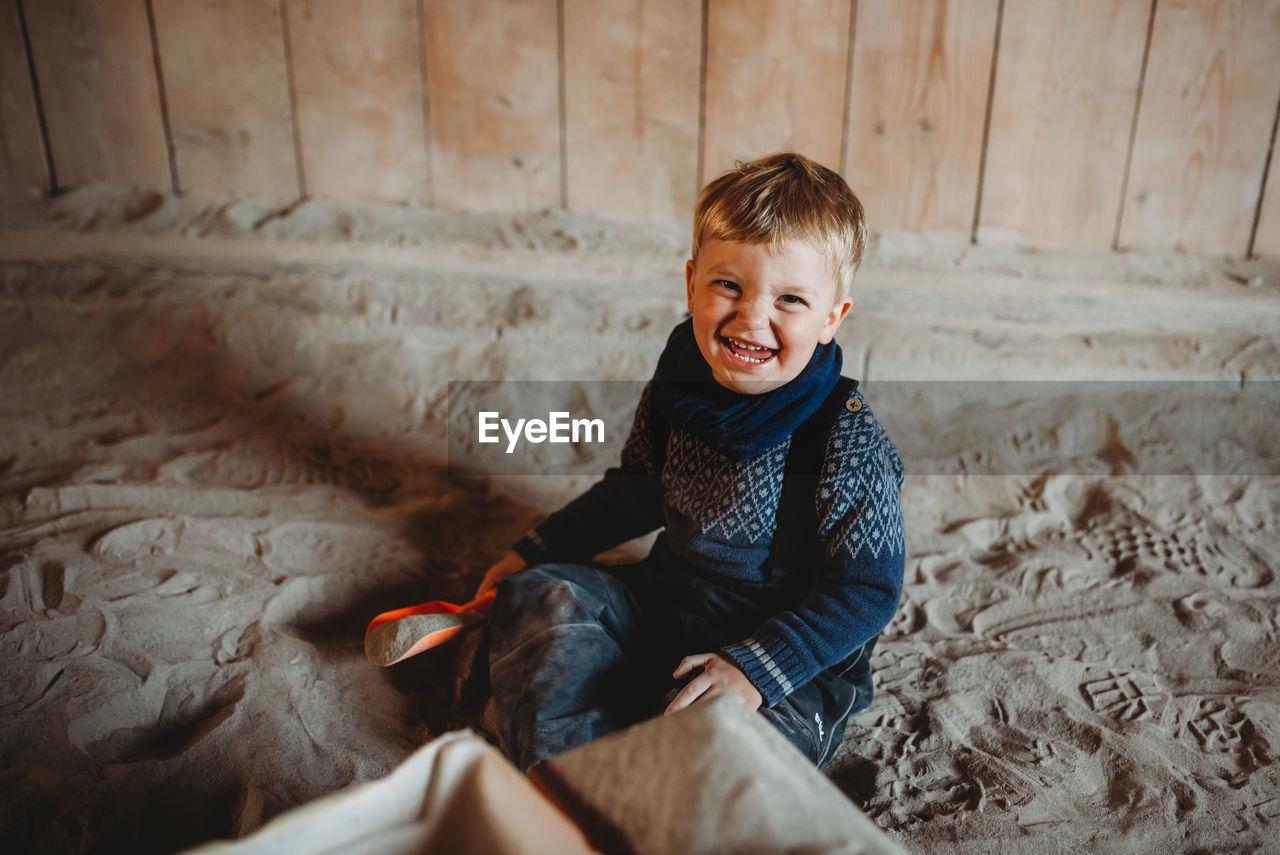 HIGH ANGLE PORTRAIT OF SMILING BOY SITTING ON SOFA