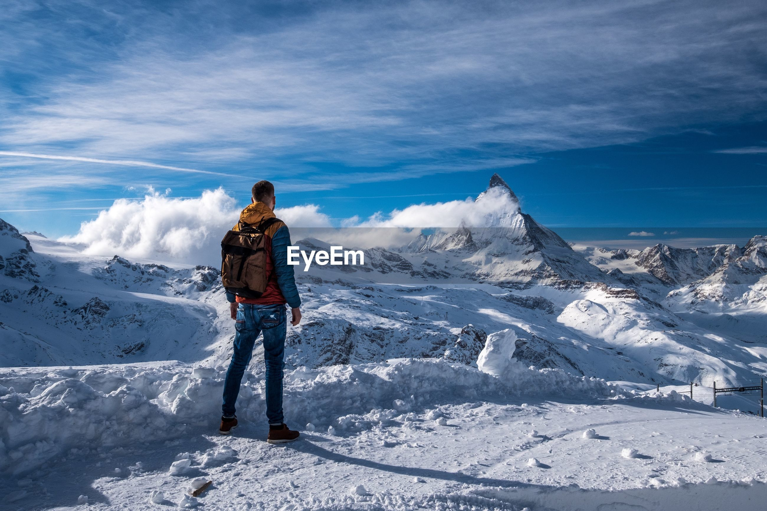 Rear view of mid adult man with backpack standing on snow against sky