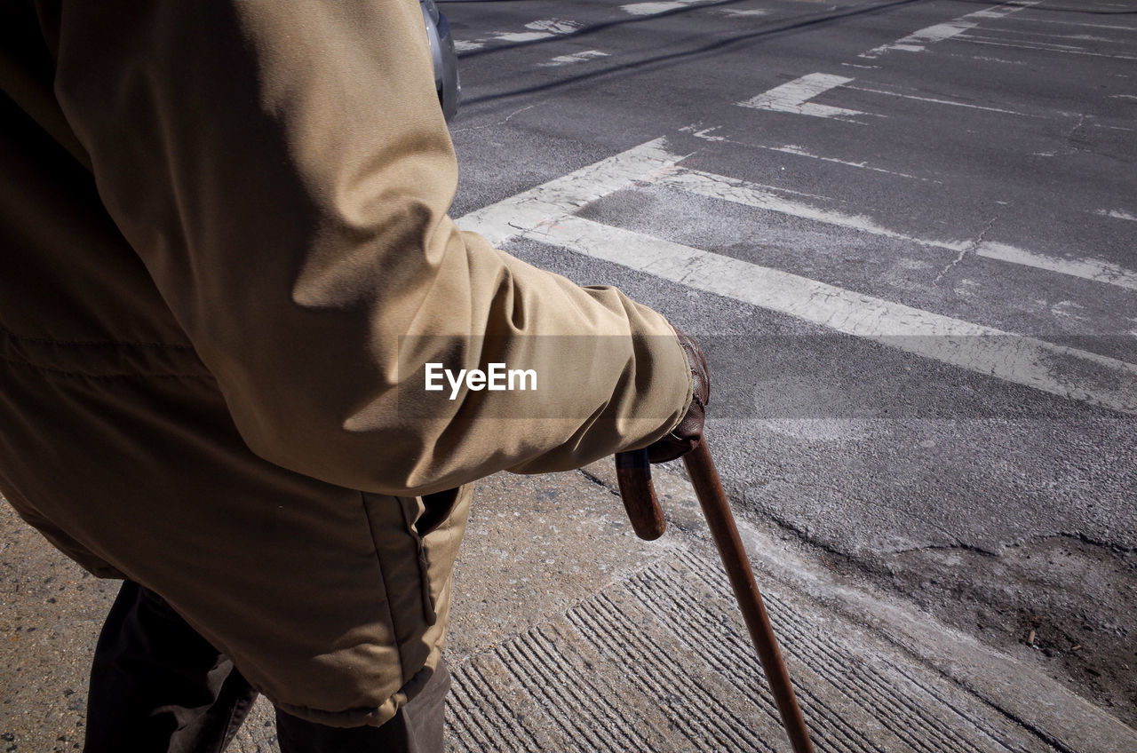 Midsection Of Senior Man Standing With Walking Cane On Sidewalk