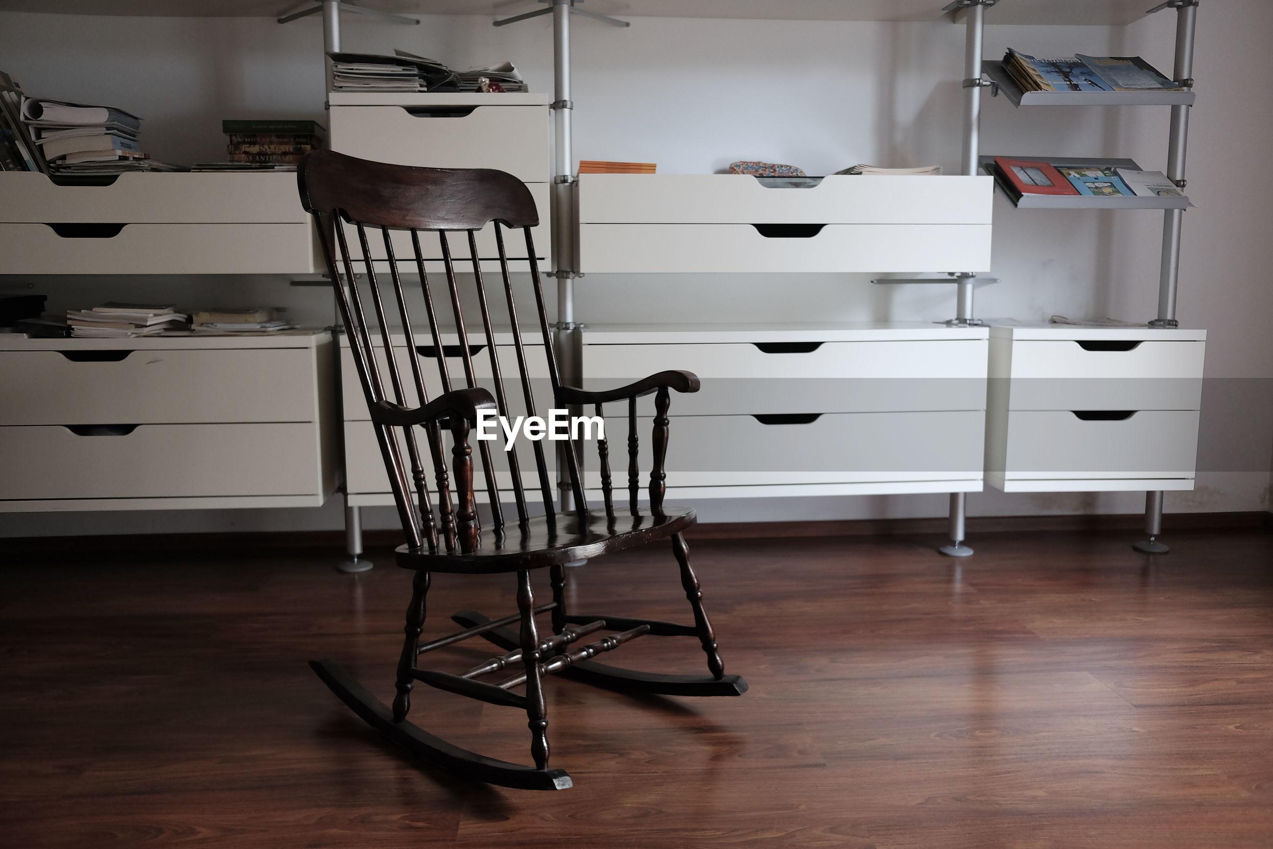 Rocking chair on hardwood floor against shelves at home