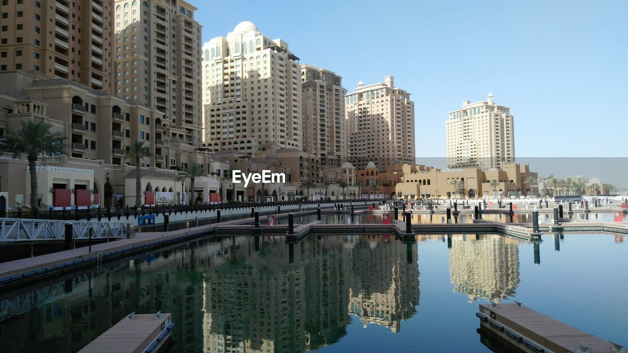 architecture, building exterior, built structure, water, city, reflection, skyscraper, waterfront, outdoors, day, cityscape, river, no people, travel destinations, modern, clear sky, nautical vessel, sky, nature