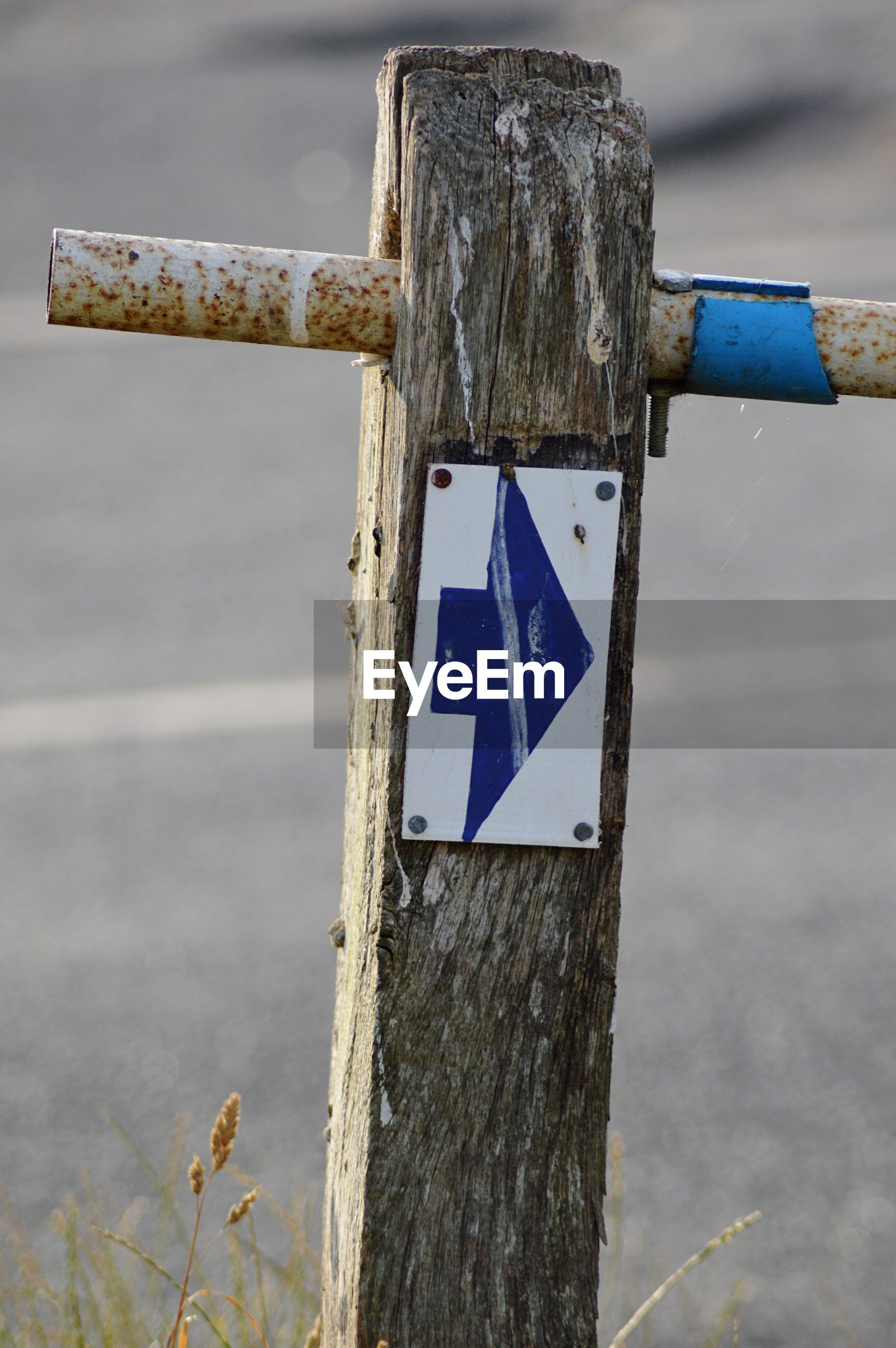 Close-up of arrow sign on wooden post on roadside