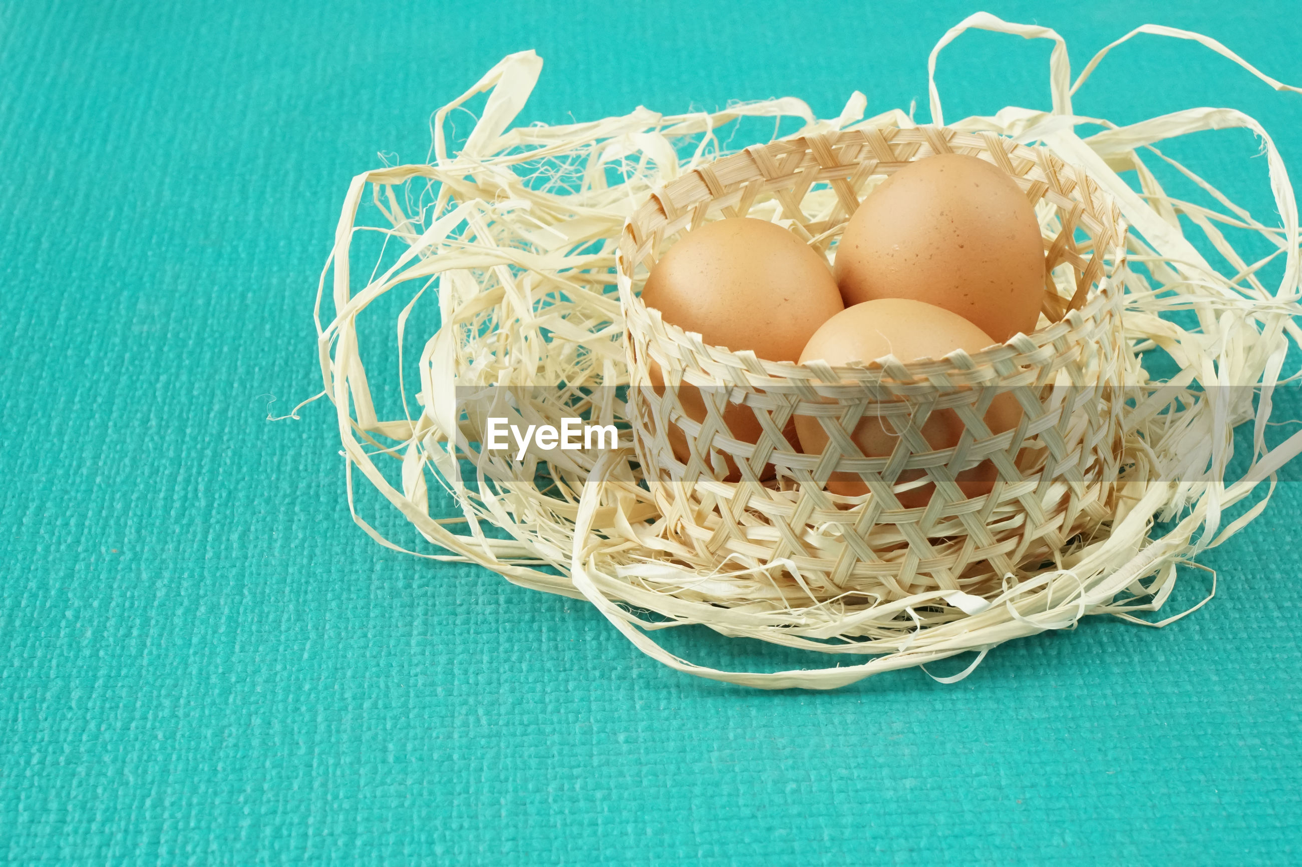 HIGH ANGLE VIEW OF EGGS IN BASKET ON BLUE TABLE