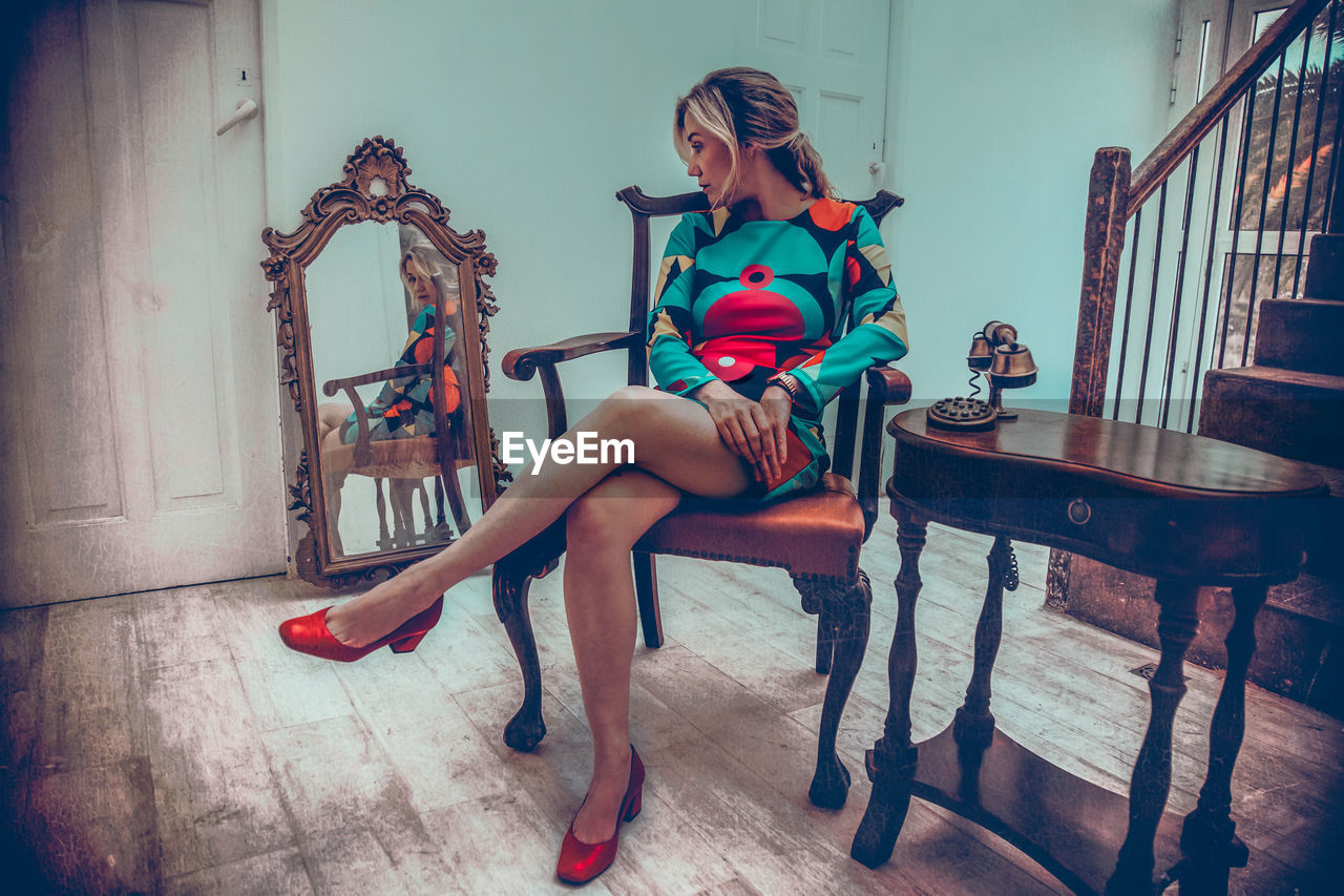 sitting, full length, young adult, seat, chair, one person, young women, women, real people, beautiful woman, fashion, lifestyles, indoors, beauty, leisure activity, clothing, high heels, hairstyle, hair, armchair