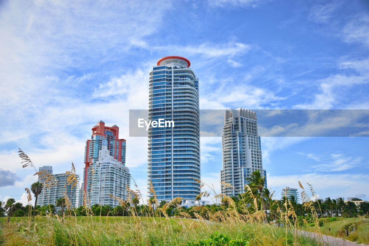 sky, architecture, building exterior, built structure, cloud - sky, grass, nature, building, office building exterior, city, plant, skyscraper, day, no people, tall - high, landscape, outdoors, field, low angle view, modern