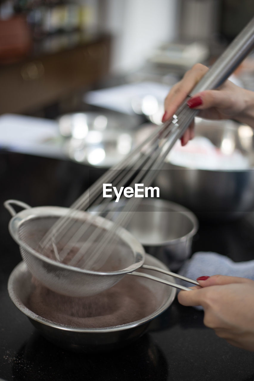 Cropped image of woman using wire whisk while baking in kitchen