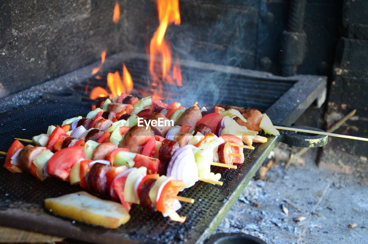barbecue grill, barbecue, heat - temperature, grilled, skewer, flame, food, preparation, food and drink, burning, meat, coal, outdoors, smoke - physical structure, preparing food, freshness, no people, kebab, sausage, healthy eating, day, serving tongs, fire pit, close-up, hot dog