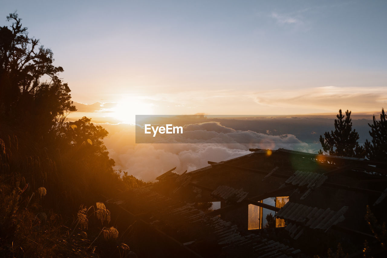 sky, sunset, architecture, building exterior, built structure, tree, sun, nature, plant, beauty in nature, building, cloud - sky, sunlight, house, orange color, scenics - nature, residential district, lens flare, outdoors, mountain, no people, bright