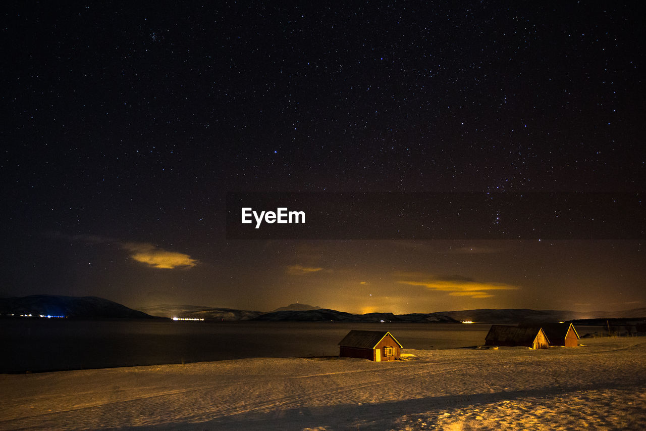 Houses On Snow Covered Lakeshore Against Star Field