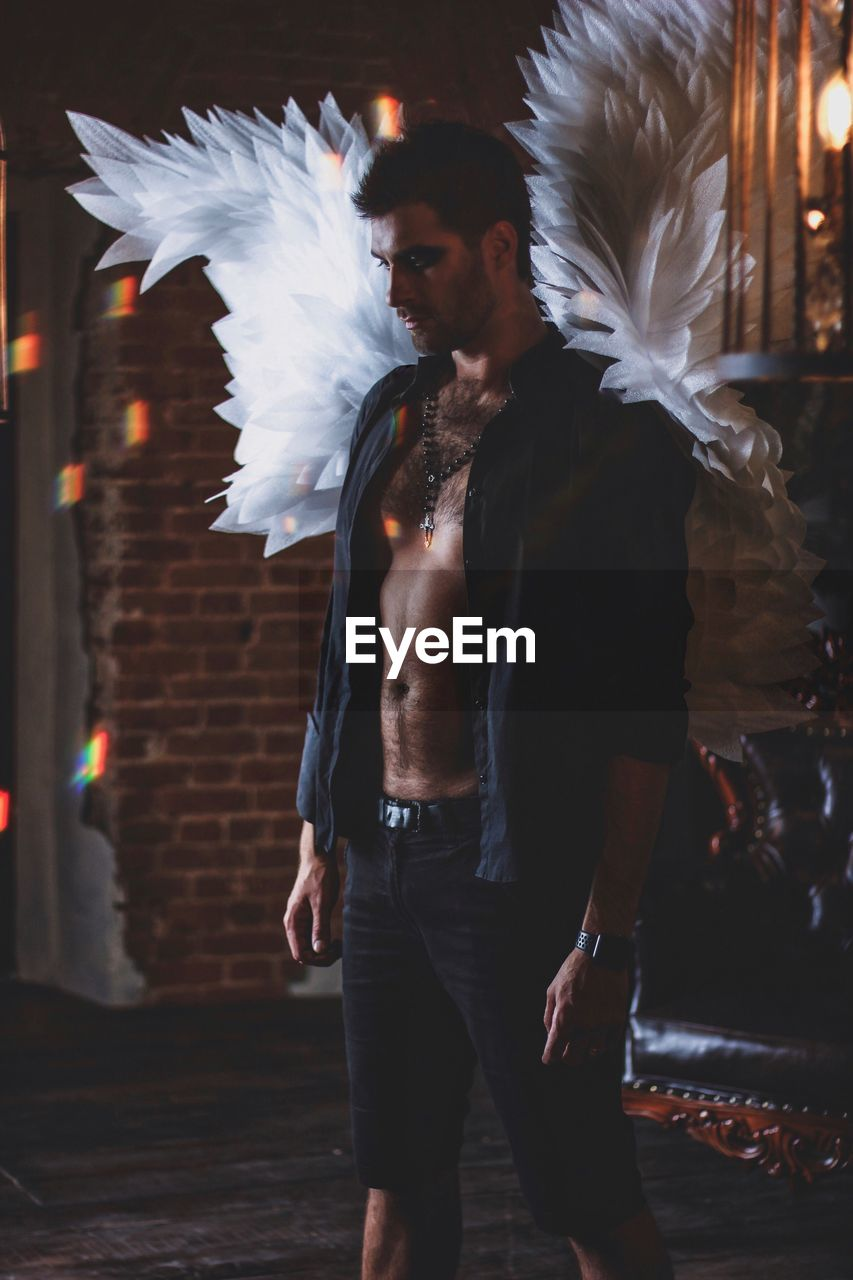 one person, real people, three quarter length, front view, standing, men, costume wing, leisure activity, lifestyles, young adult, feather, males, young men, casual clothing, adult, motion, shirtless, focus on foreground, costume, angel