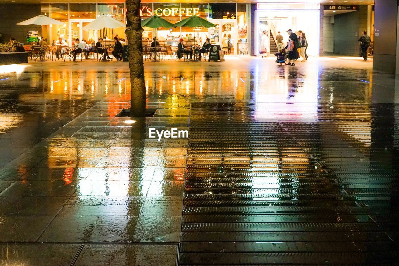reflection, real people, lifestyles, illuminated, walking, women, water, retail, night, consumerism, wet, leisure activity, men, large group of people, customer, architecture, outdoors, built structure, building exterior, full length, city, adult, people, adults only