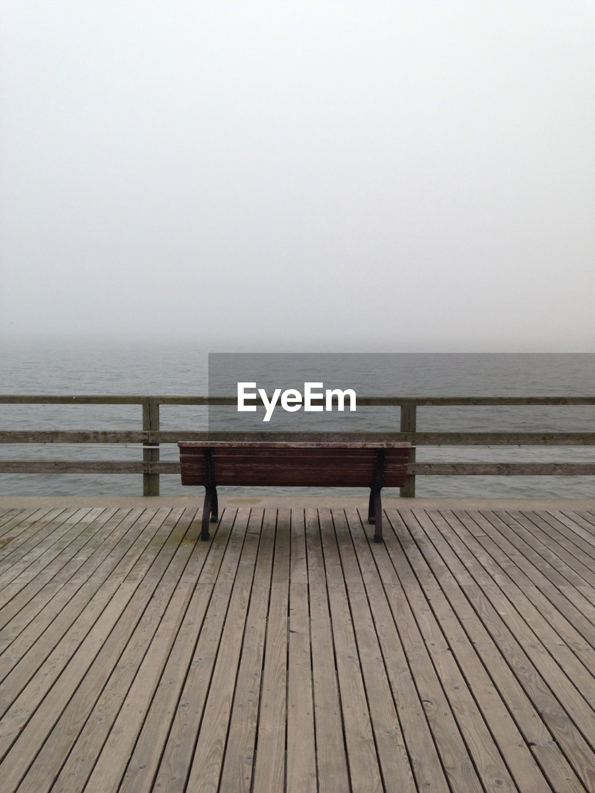 Empty park bench on ahlbeck pier in front of sea during foggy weather