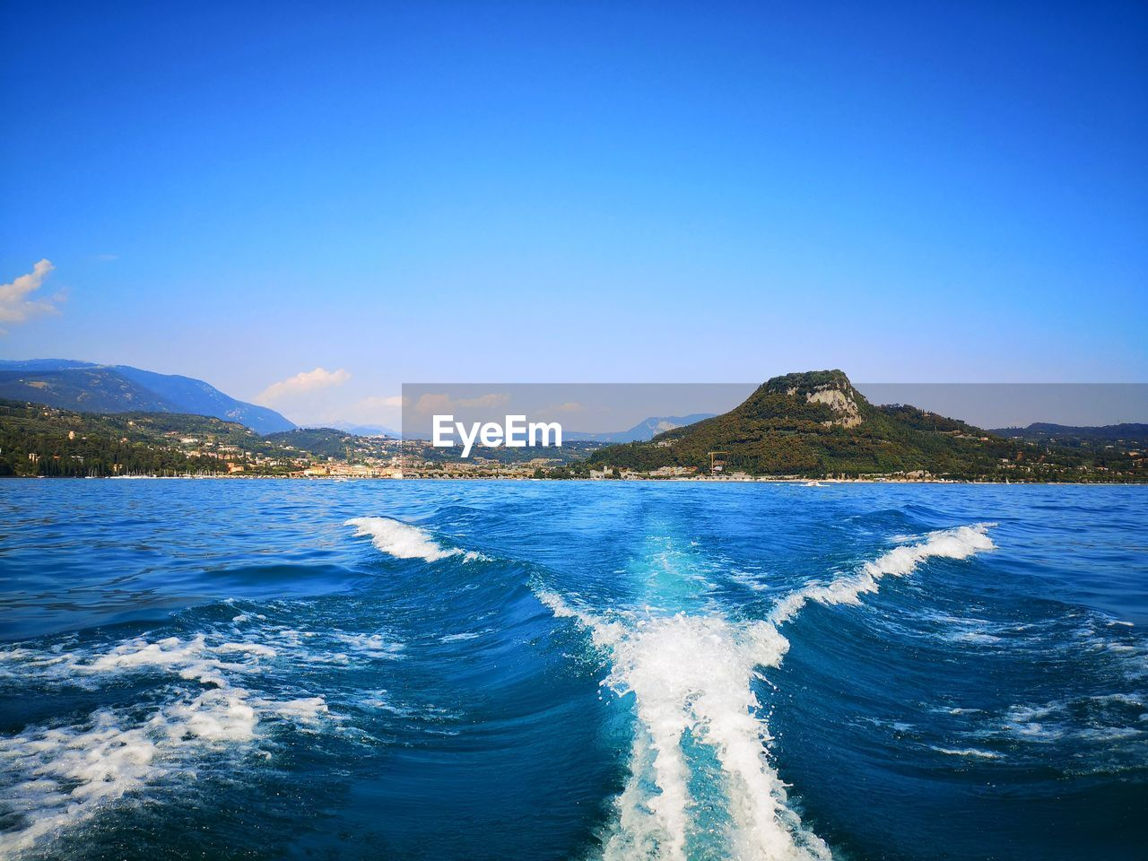 water, sea, beauty in nature, blue, sky, scenics - nature, motion, copy space, mountain, waterfront, no people, wave, nature, aquatic sport, wake - water, clear sky, tranquil scene, idyllic, sport, outdoors