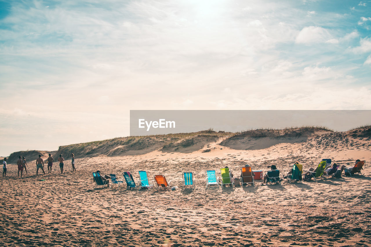 People Relaxing On Wooden Chairs At Beach Against Sky