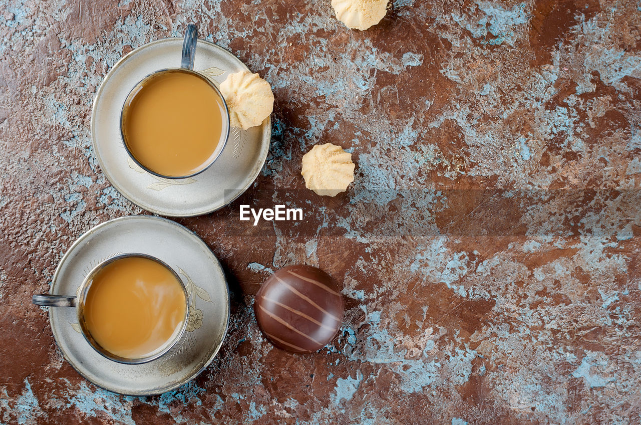 Directly above shot of donut and coffee cups on textured table