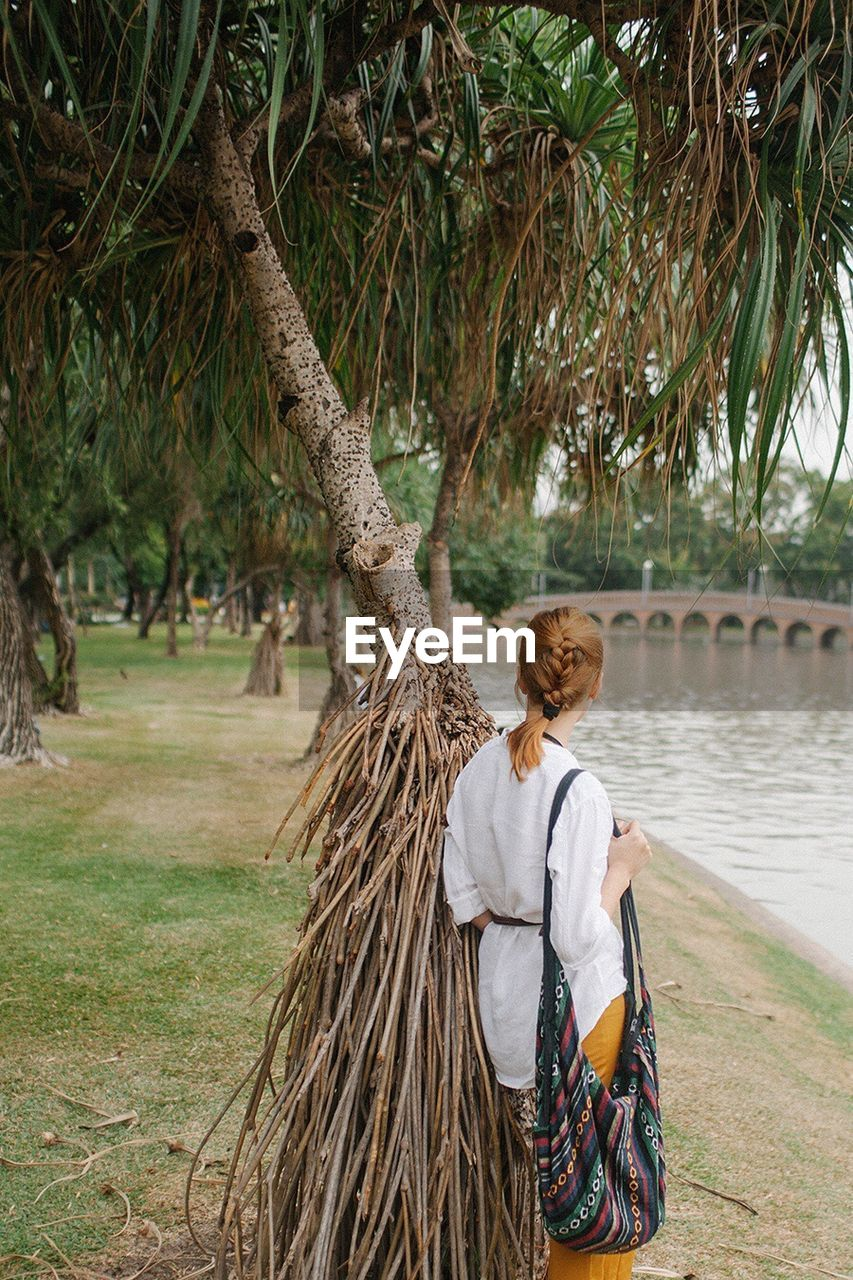 Woman standing under tree