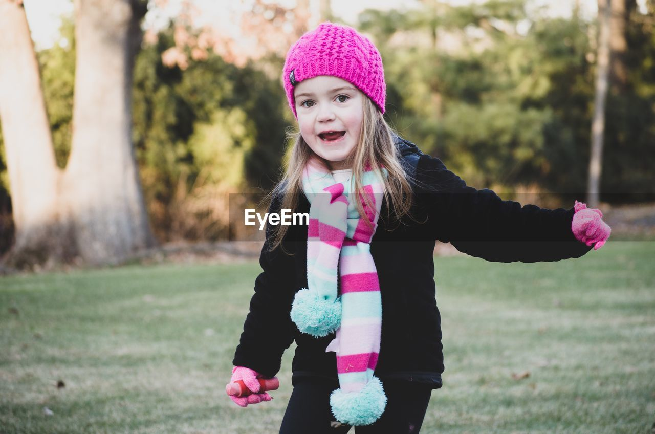pink color, girls, childhood, one person, real people, knit hat, leisure activity, focus on foreground, happiness, day, outdoors, elementary age, smiling, grass, lifestyles, warm clothing, nature, tree, close-up, people