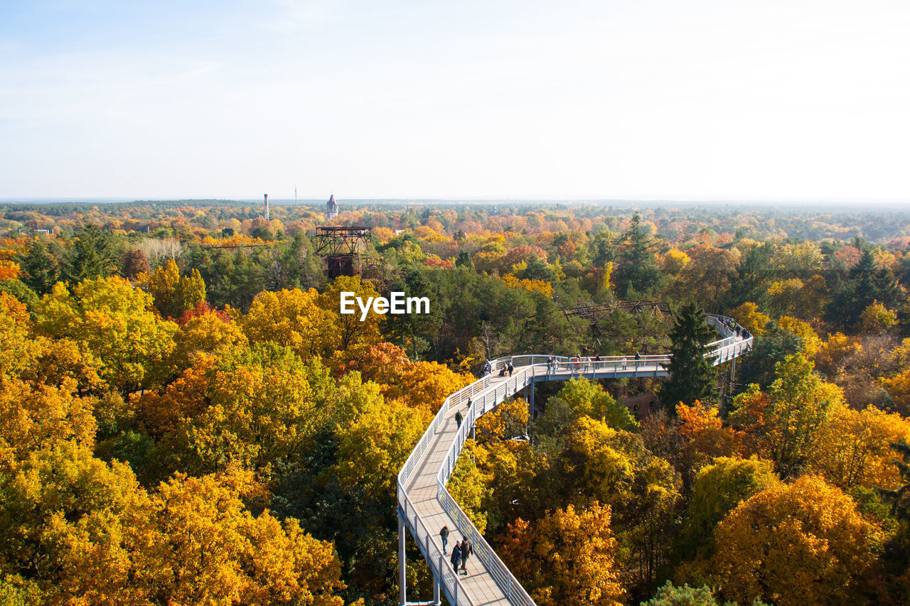 High angle view of footbridge amidst trees against sky during autumn