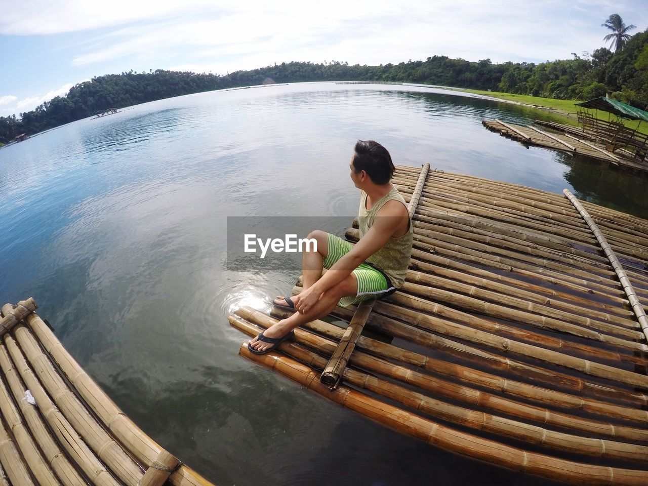 High angle view of man sitting on wooden raft