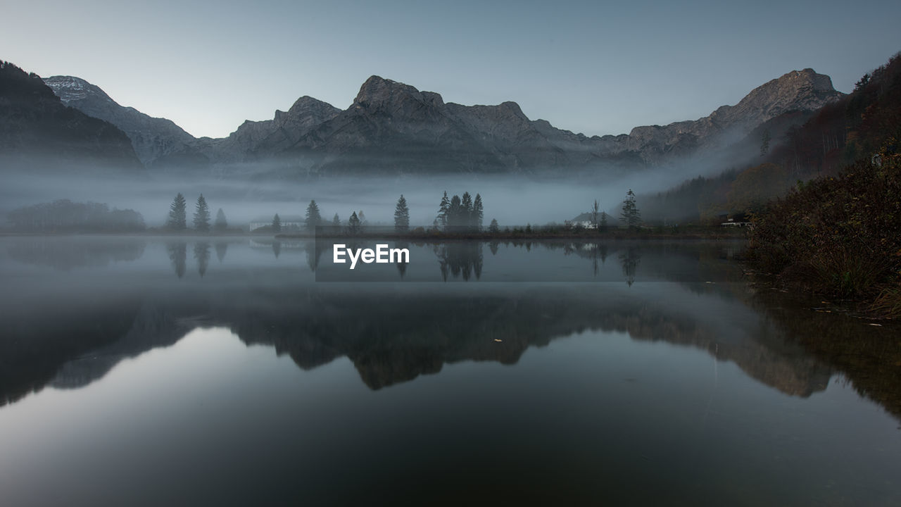 sky, water, lake, reflection, tranquility, mountain, tranquil scene, beauty in nature, scenics - nature, waterfront, nature, fog, non-urban scene, no people, mountain range, day, idyllic, outdoors, reflection lake, hazy