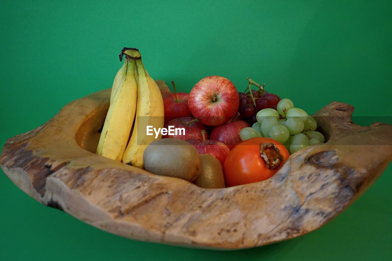 fruit, healthy eating, food and drink, food, wellbeing, freshness, banana, still life, colored background, apple - fruit, no people, indoors, close-up, table, studio shot, high angle view, green background, container, green color, bowl