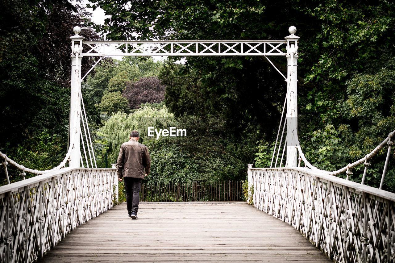 Rear View Of Man Walking On Footbridge In Public Park