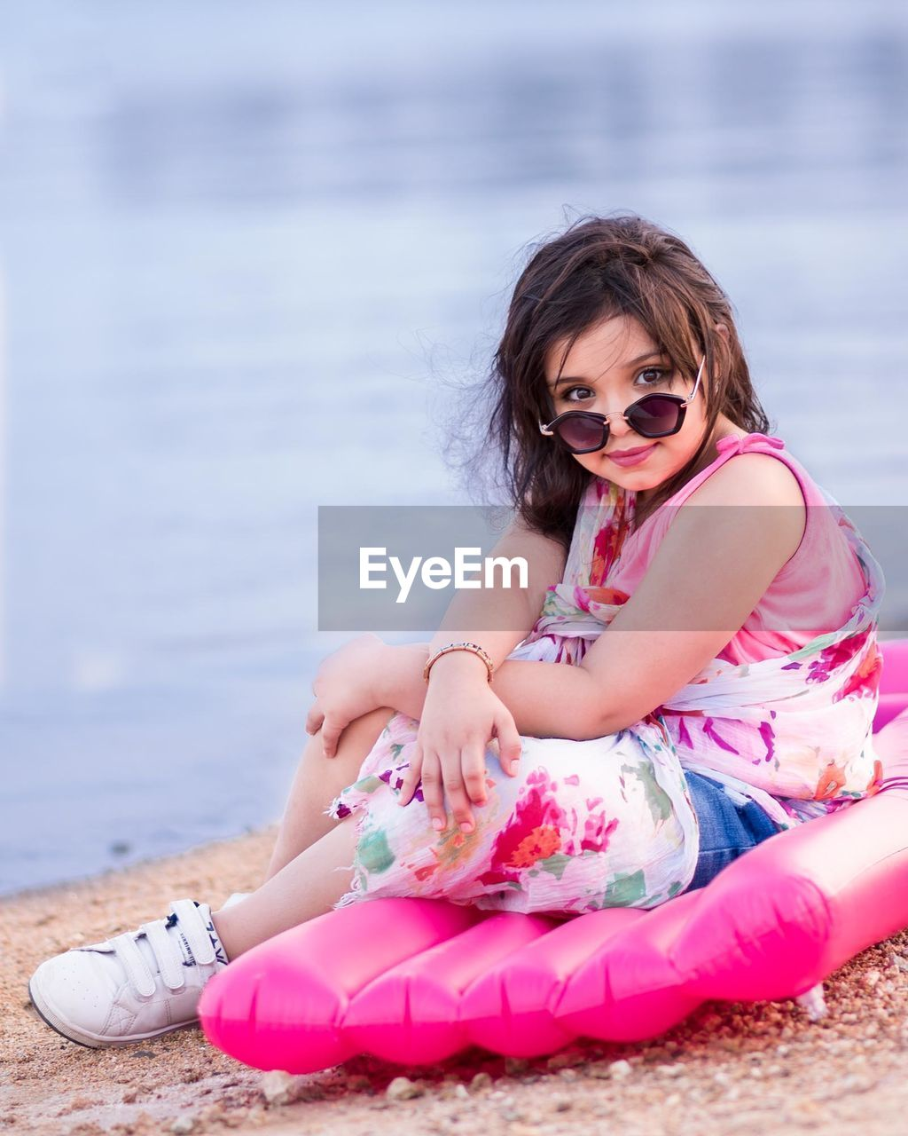 Portrait Of Girl In Sunglasses Sitting At Beach