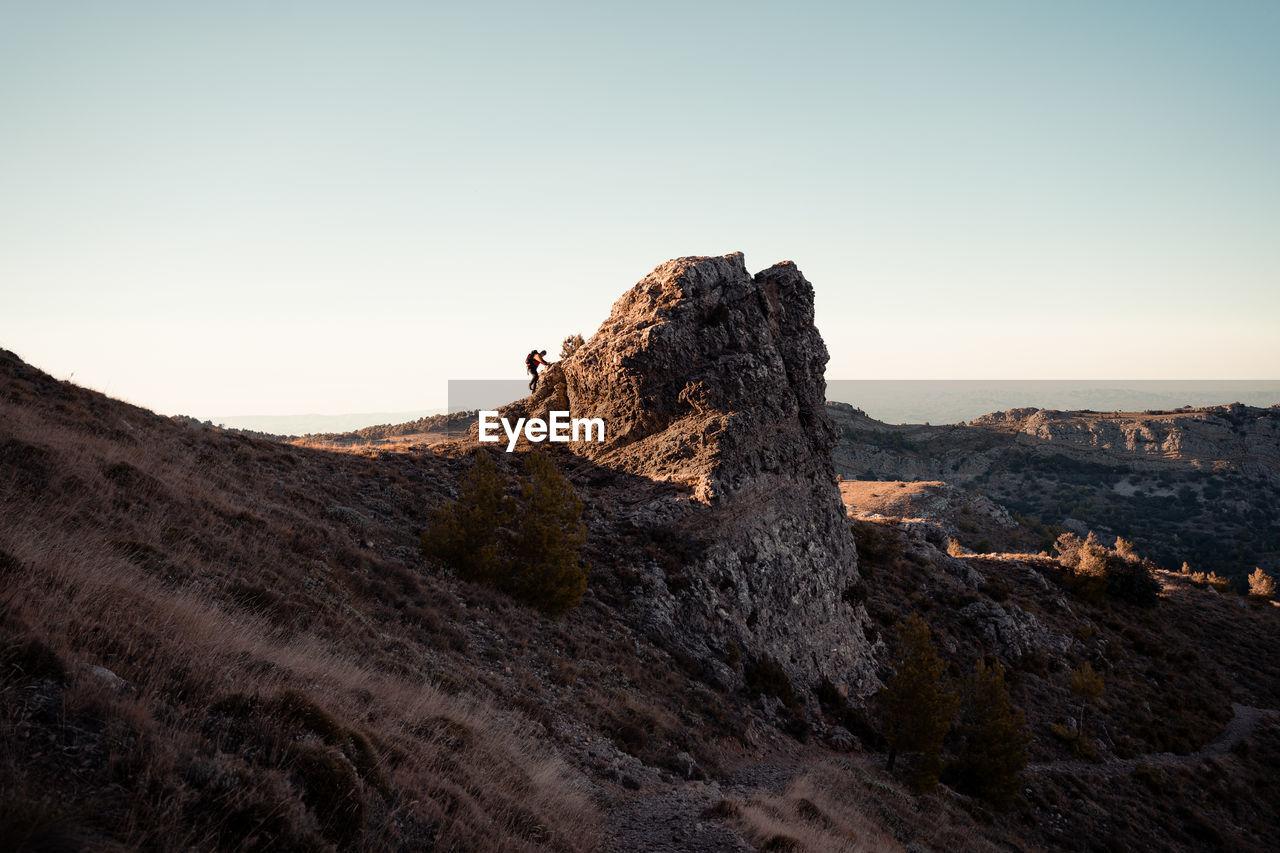 Full length of man climbing on rock against sky