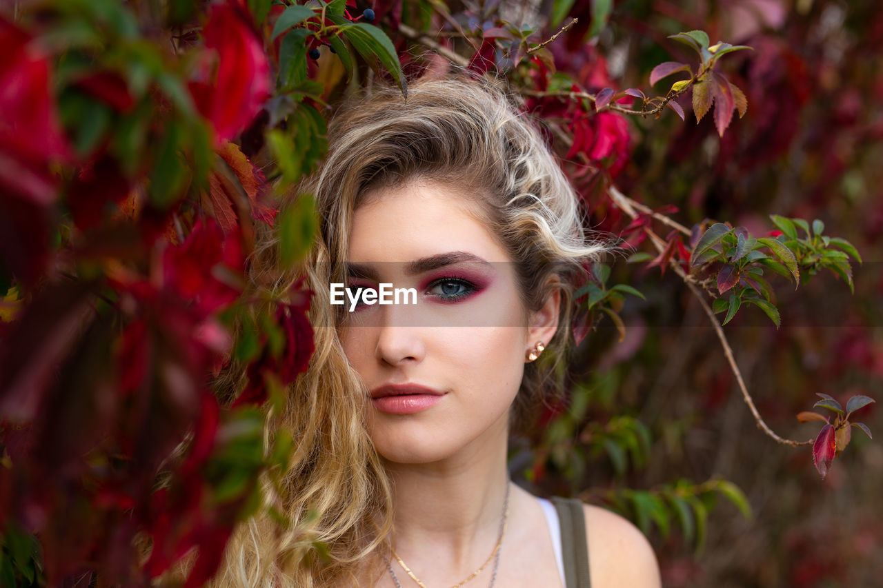 Portrait of beautiful young woman with make-up by plants