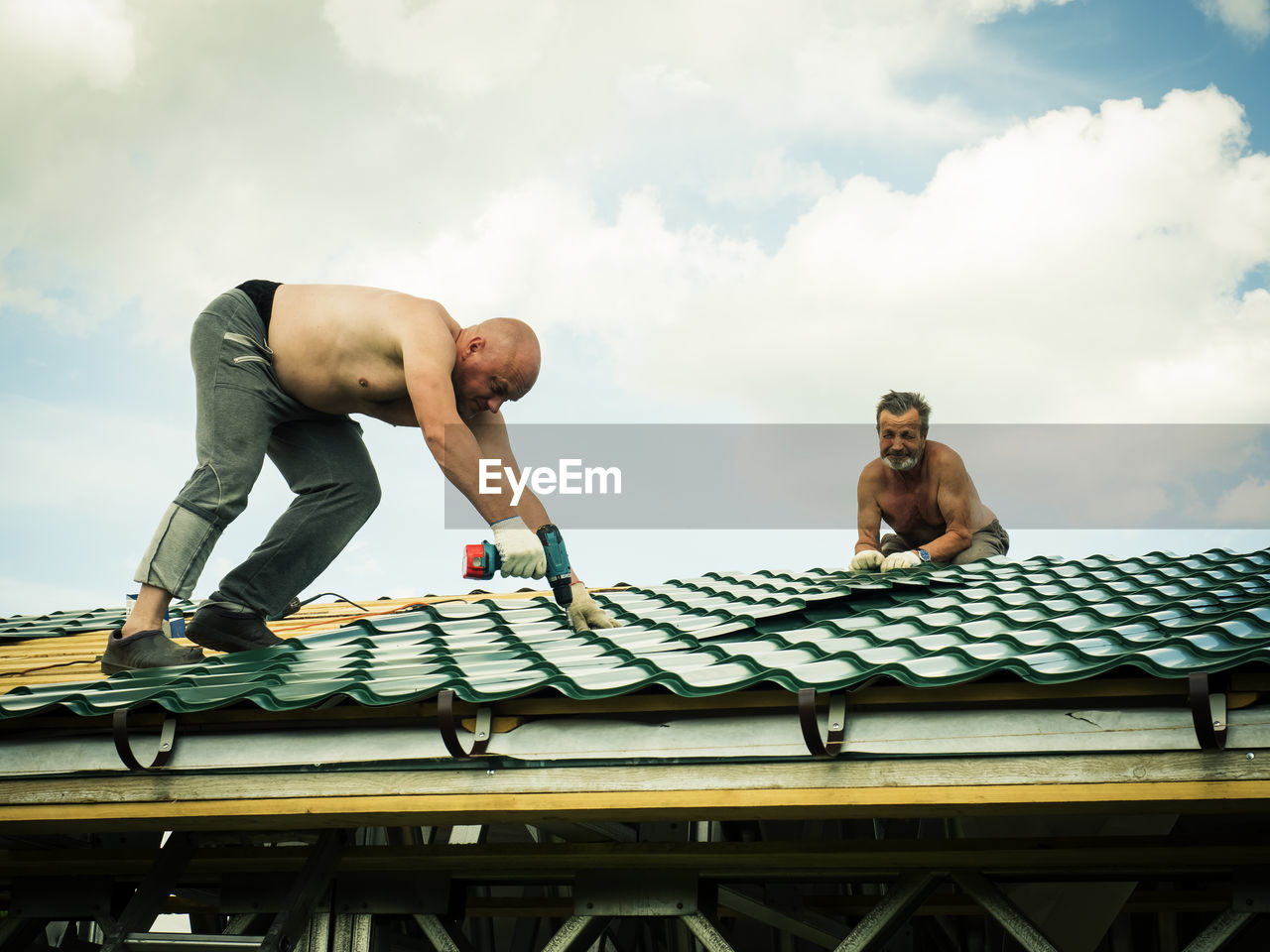Shirtless Men Working On Roof Against Sky
