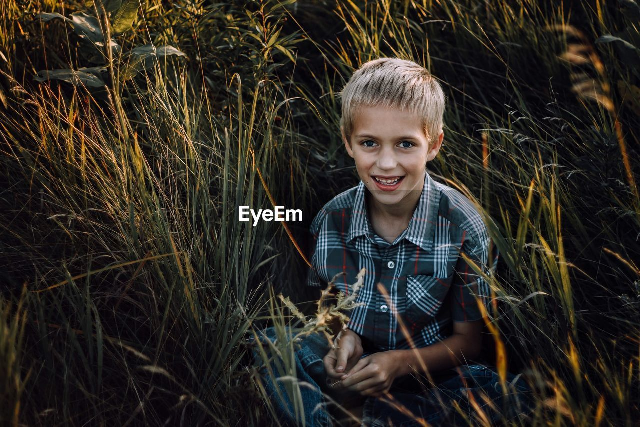 High angle portrait of smiling boy sitting on field amidst plants