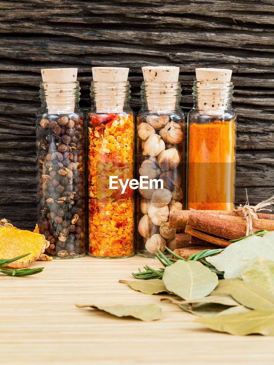 Close-up of various spices in glass bottles on table