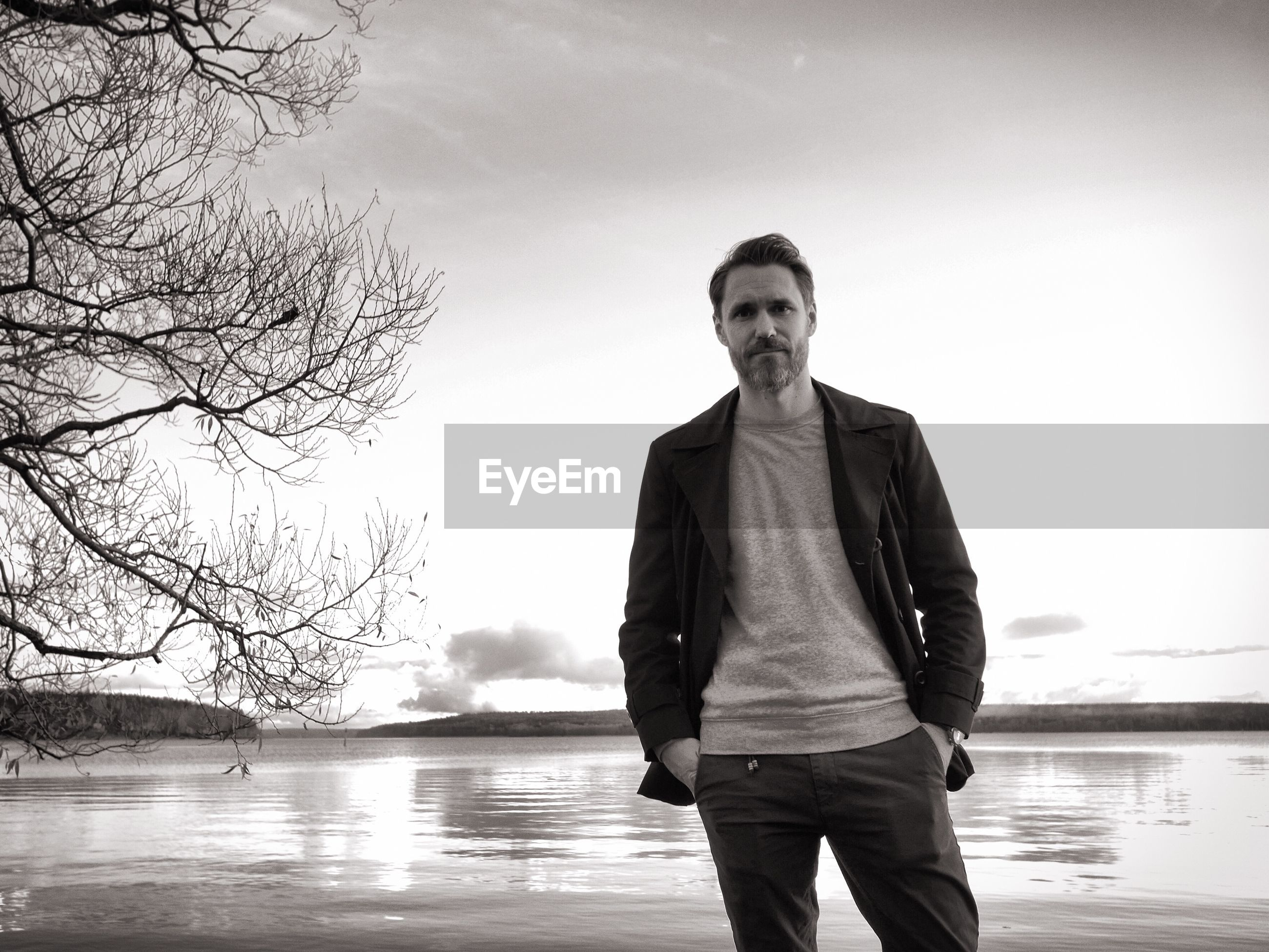 Portrait of mid adult man standing against lake