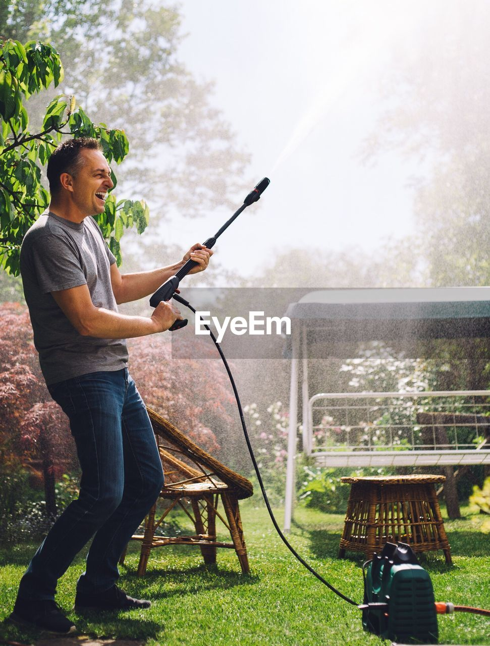 Cheerful Man With Garden Hose At Back Yard