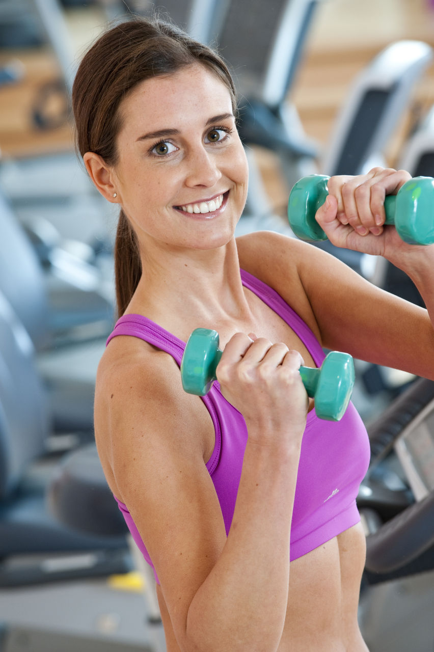 Portrait Of Smiling Young Woman Holding Dumbbells At Gym