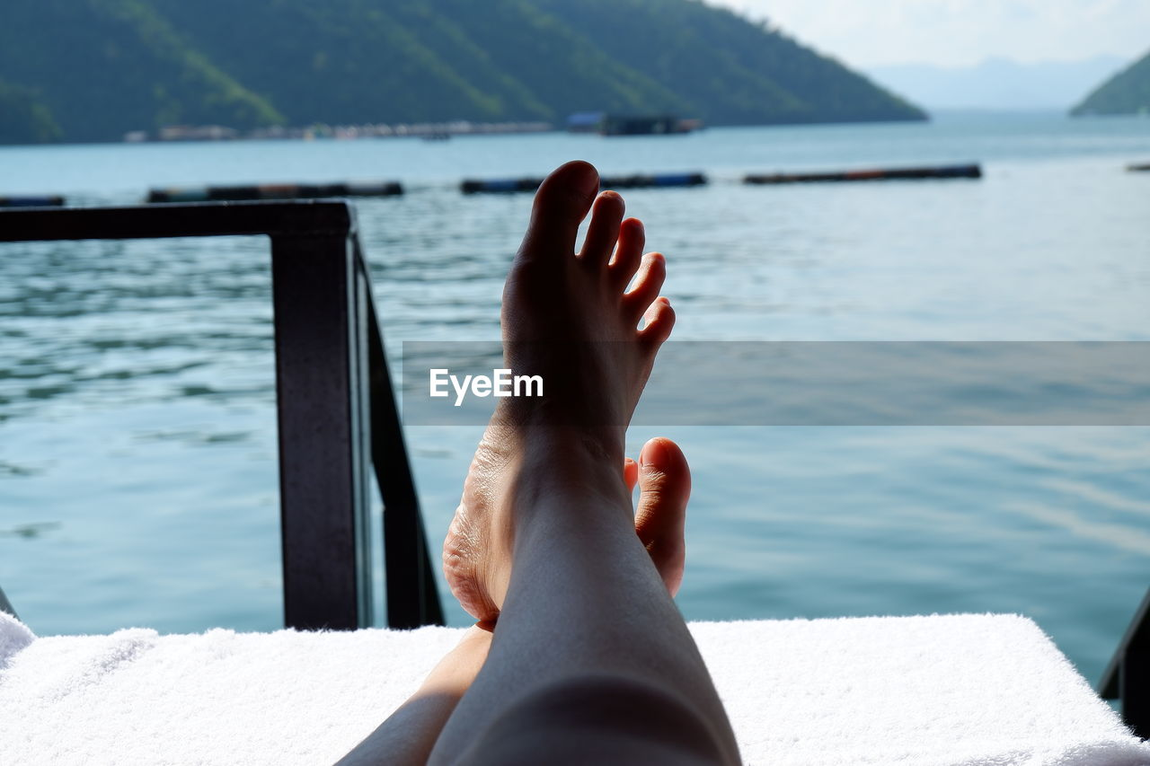 Low section of person relaxing by sea