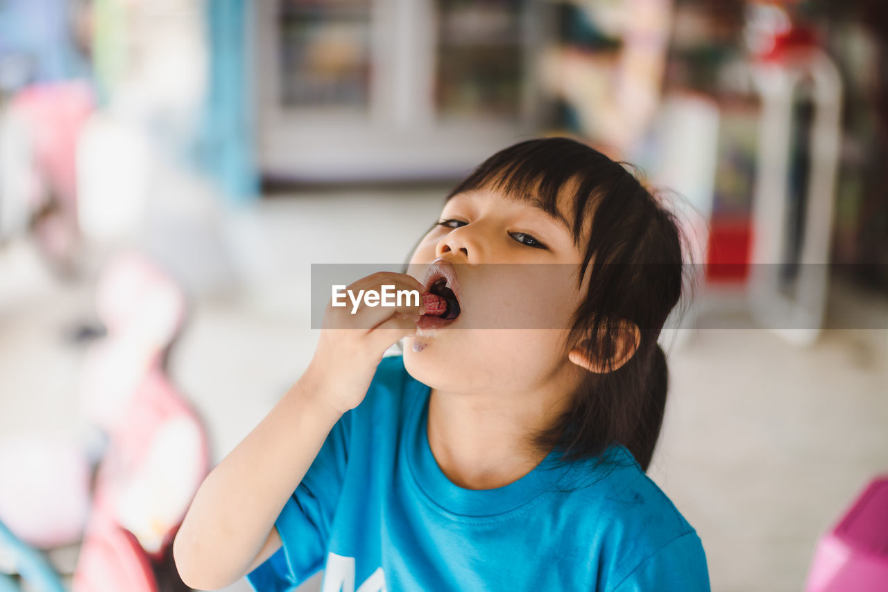 child, childhood, headshot, focus on foreground, real people, one person, portrait, girls, females, indoors, lifestyles, innocence, women, casual clothing, mouth, mouth open, leisure activity, looking, hairstyle