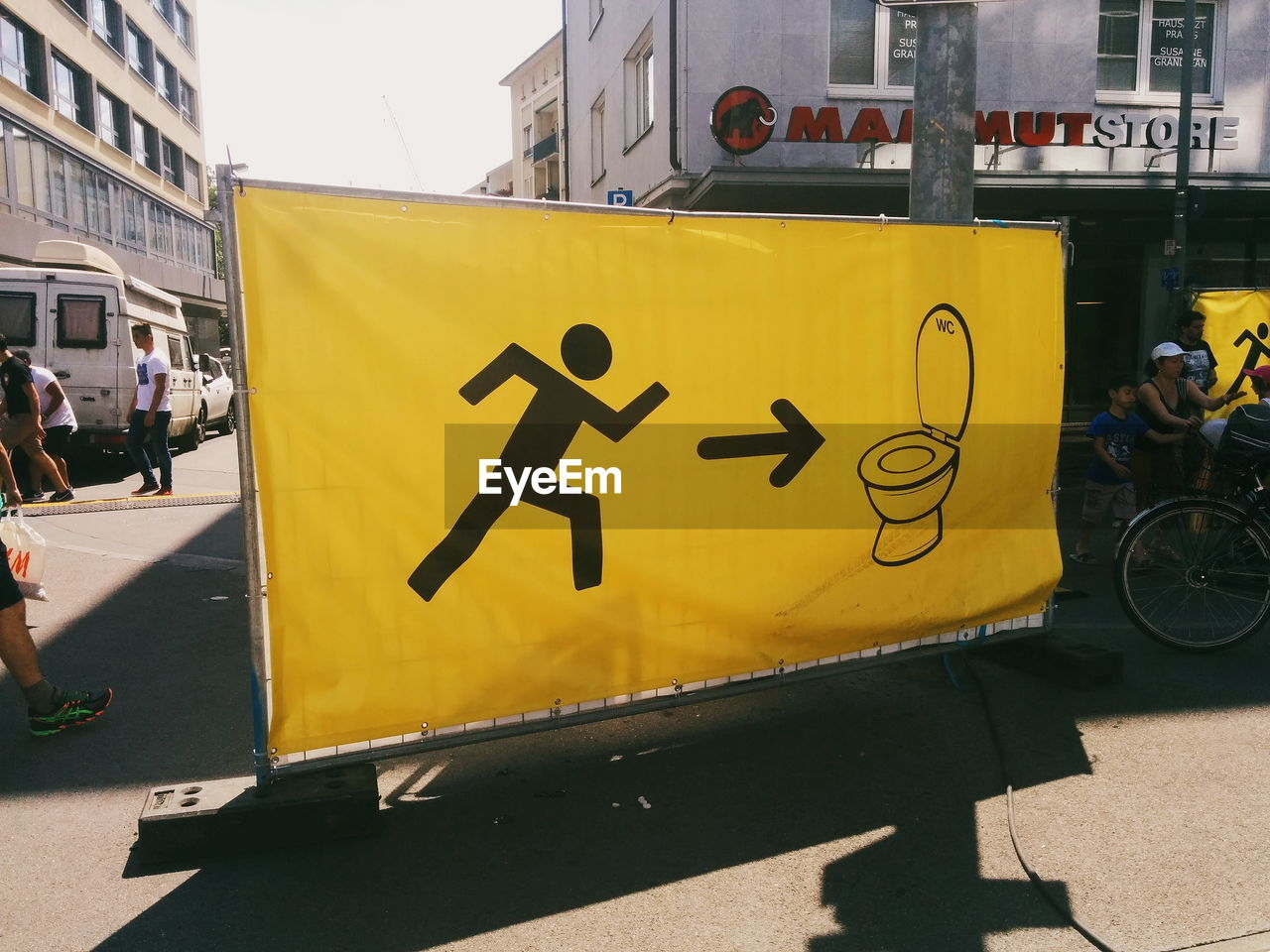 yellow, architecture, built structure, communication, day, building exterior, outdoors, bicycle, road sign, city, no people