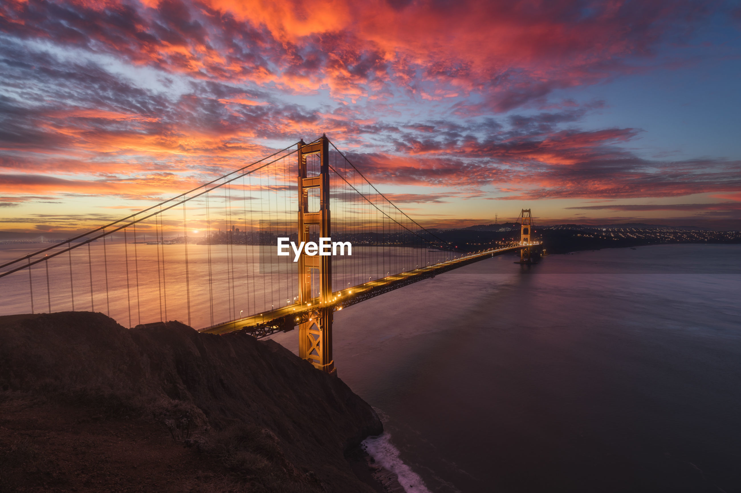 Suspension bridge over river during sunset