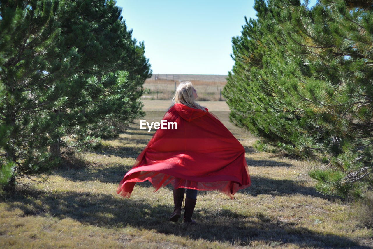 one person, rear view, plant, red, real people, full length, nature, land, tree, women, day, field, walking, lifestyles, clothing, leisure activity, adult, growth, sunlight, outdoors, hairstyle