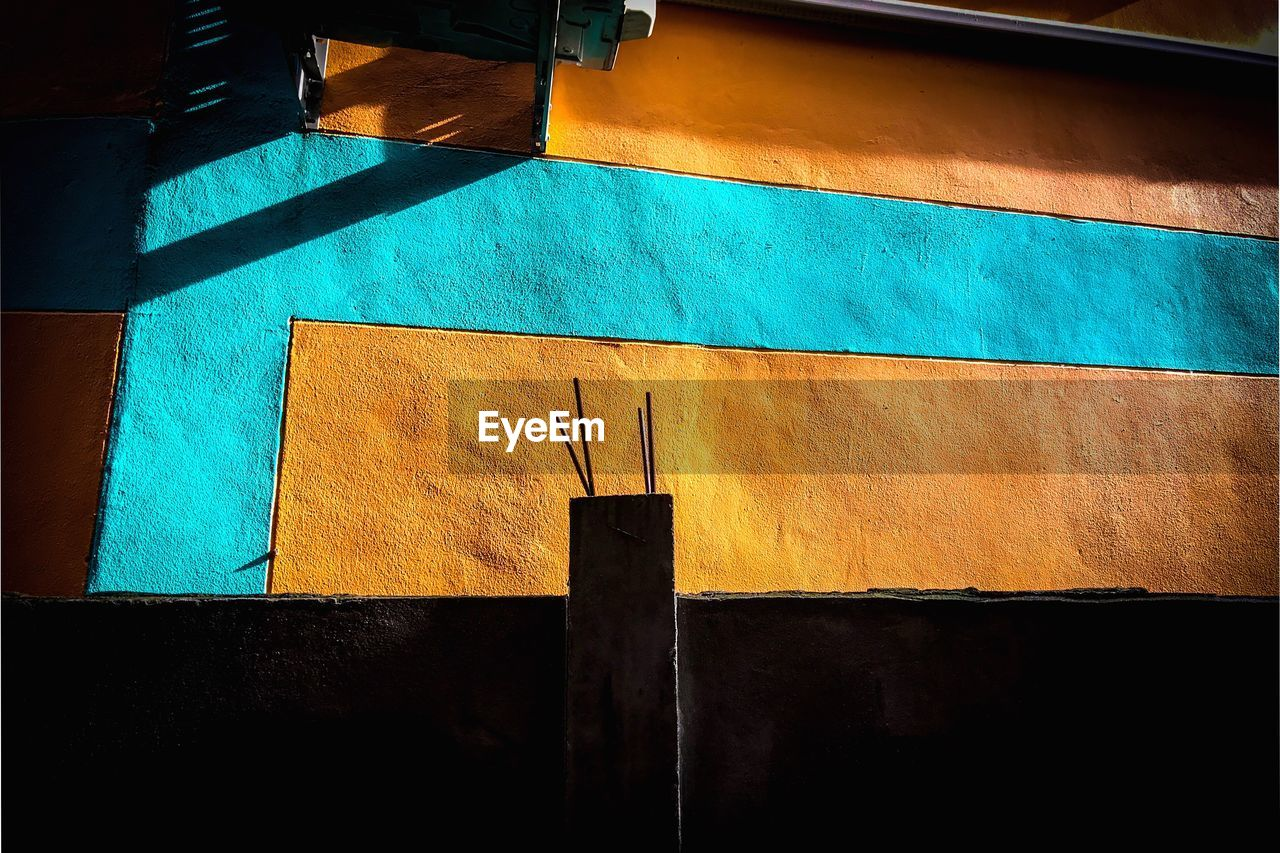 built structure, architecture, blue, no people, building exterior, low angle view, wall - building feature, day, sunlight, wood - material, yellow, shadow, outdoors, pattern, building, nature, striped, wall, close-up, turquoise colored