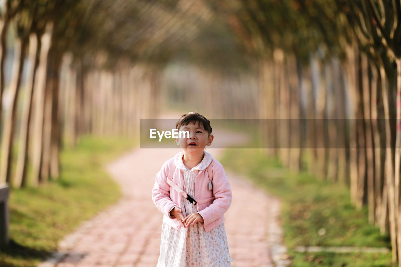 Cute Girl Standing On Footpath Amidst Trees
