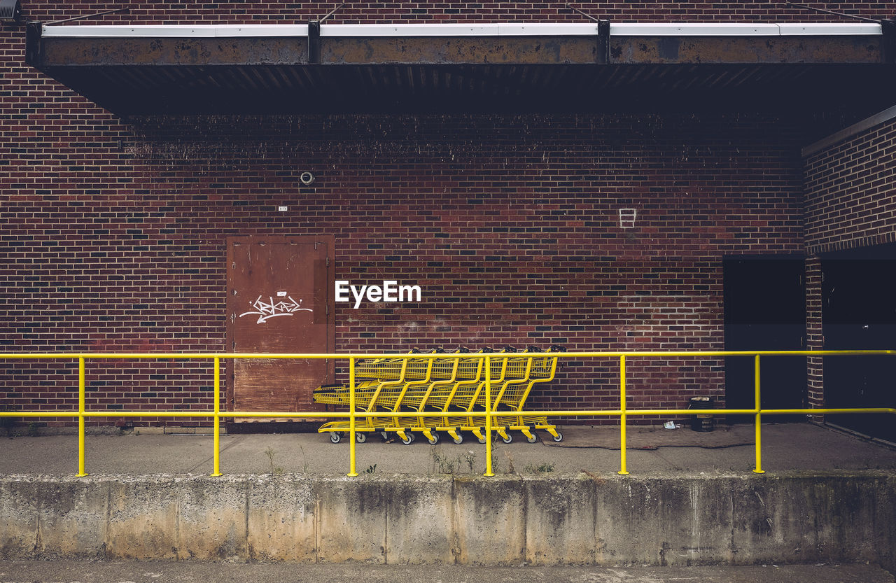 Yellow shopping carts against red brick wall